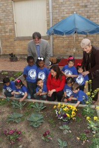 Dr. Jeff Crane (standing, left); Alejandra Barraza (kneeling); and Dr. Mary Ruth Moore (standing, right); share a  moment with students in  Carroll's vegetable garden.