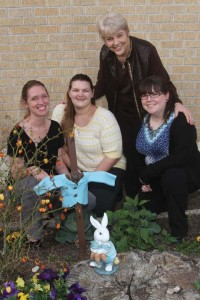 (Pictured L-R) UIW students Kaime Roe, Kerri Rodriguez, and Megan Wellington, share a photo with Dr. Mary Ruth Moore (standing) with the Peter Rabbit statue in the  garden.  The small jacket was handmade by Wellington.