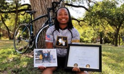 Skelton holds her photo with Obama and Biden at the White House as well as her service award.