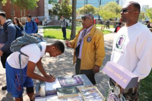 A student signs up for information at the Omega Psi Phi table during the Greeks in the Circle event at UIW.
